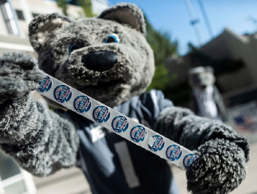 "Alphie, Jr., the Wolf Pack mascot, holds up a roll of ""I voted"" stickers"