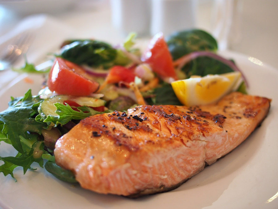 A plate of cooked salmon with vegetables.