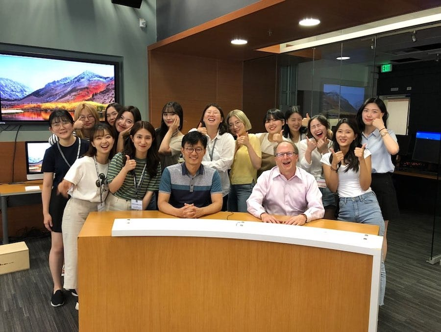 A group of South Korean students pose with Dean Stavitsky behind the anchor desk in the Reynolds Media Lab.