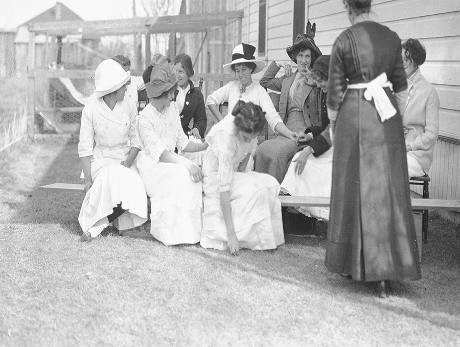 black and white photograph of a group of women seated outside; one women wearing apron with back turned to camera.