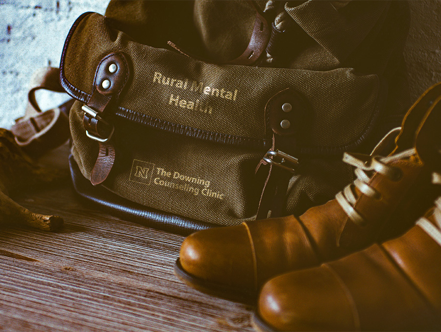 """Photo of bag and shoes. The words """"Rural Mental Health"""" are on the bag with the Downing Counseling Clinic logo"""