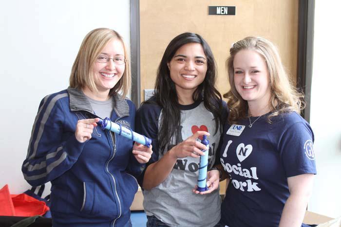 Three female students wearing University of Nevada, Reno and I love social work shirts
