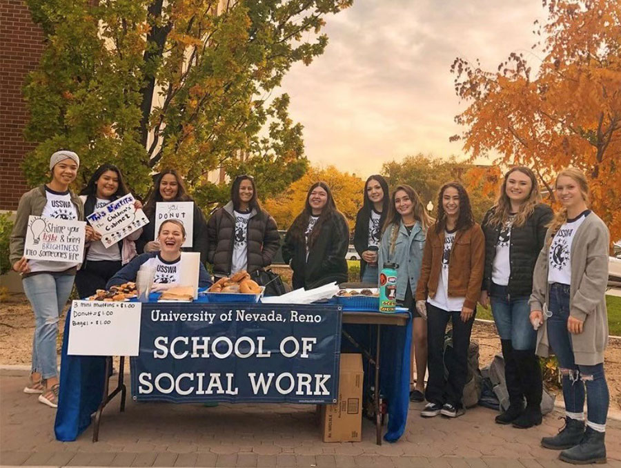 A group of University students with the School of Social Work stand around a table with signs and donuts