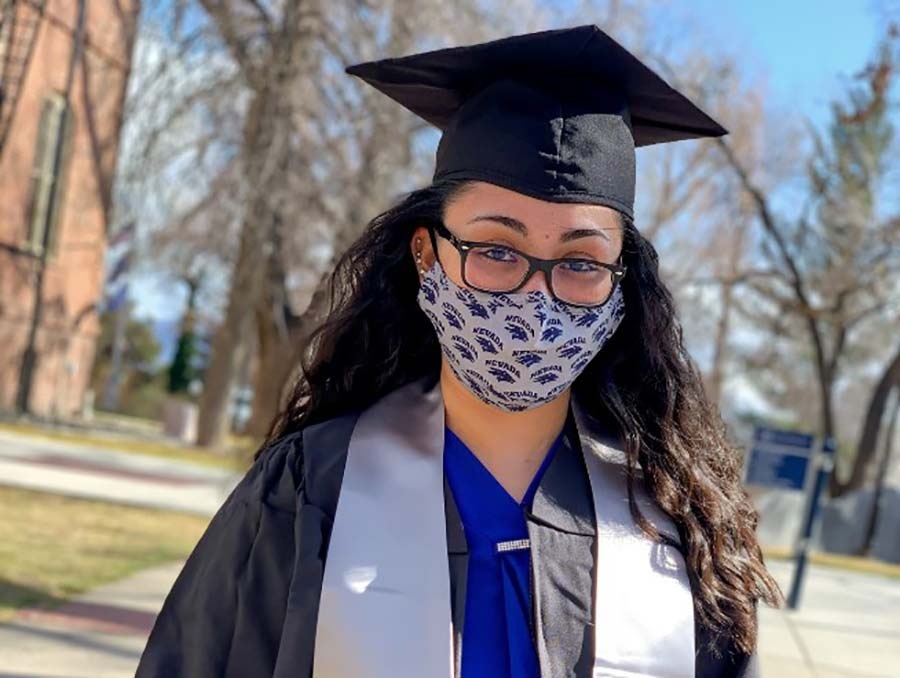 University of Nevada, Reno graduate with grad cap and facial covering on the historic Quad