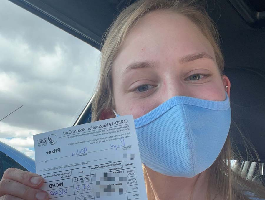 Malia Pruyn holding a COVID-19 Vaccination card