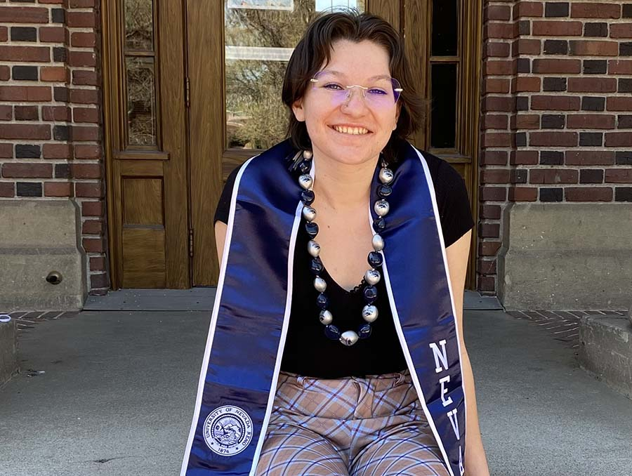 Senior Scarlett Boling sits on steps smiling for graduation pictures