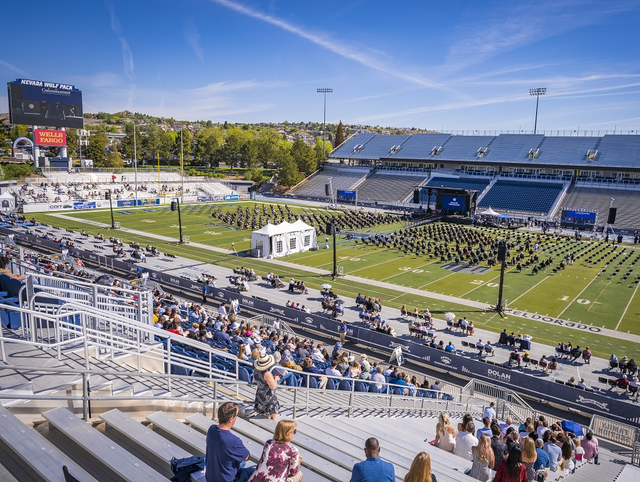 A view of Spring 2021 Commencement from the stands of Mackay Stadium, showing the crowd and all graduates socially distanced, the stage, and really everything else