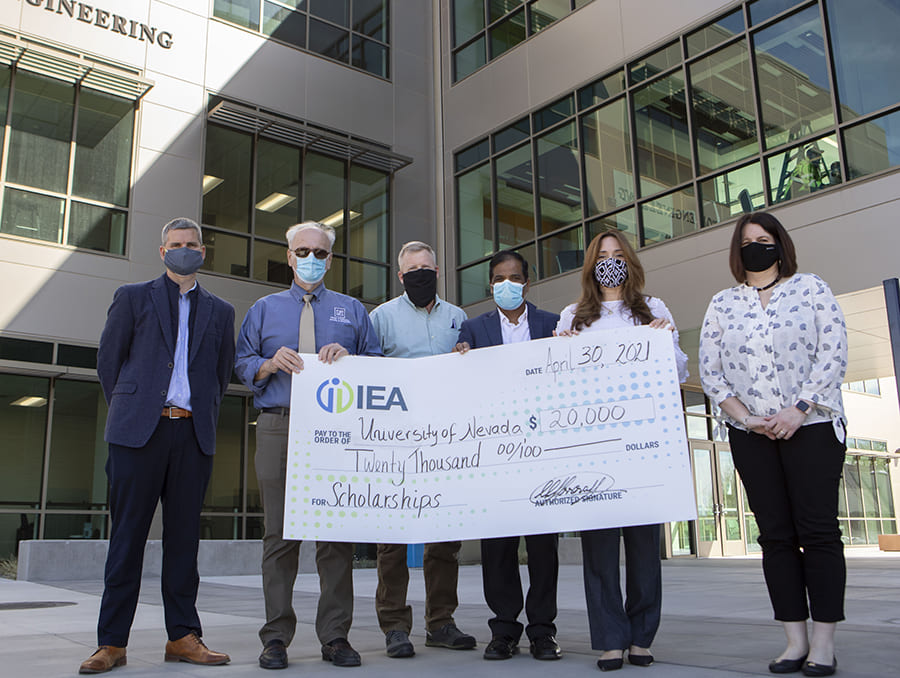People standing in front of the William N. Pennington Engineering Building for a check presentation.