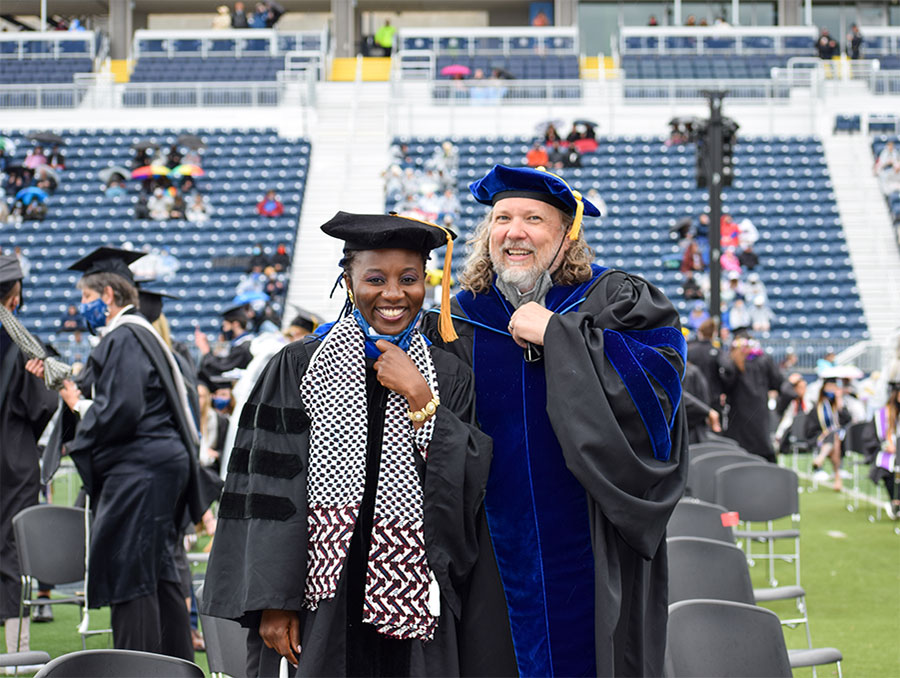 Judge Ari Tobi-Aiyemo stands next to Shawn Marsh in commencement attire on the field during graduation
