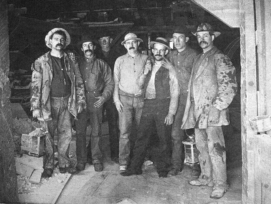 Group of seven miners stand at the entrance of a mine located in Nevada