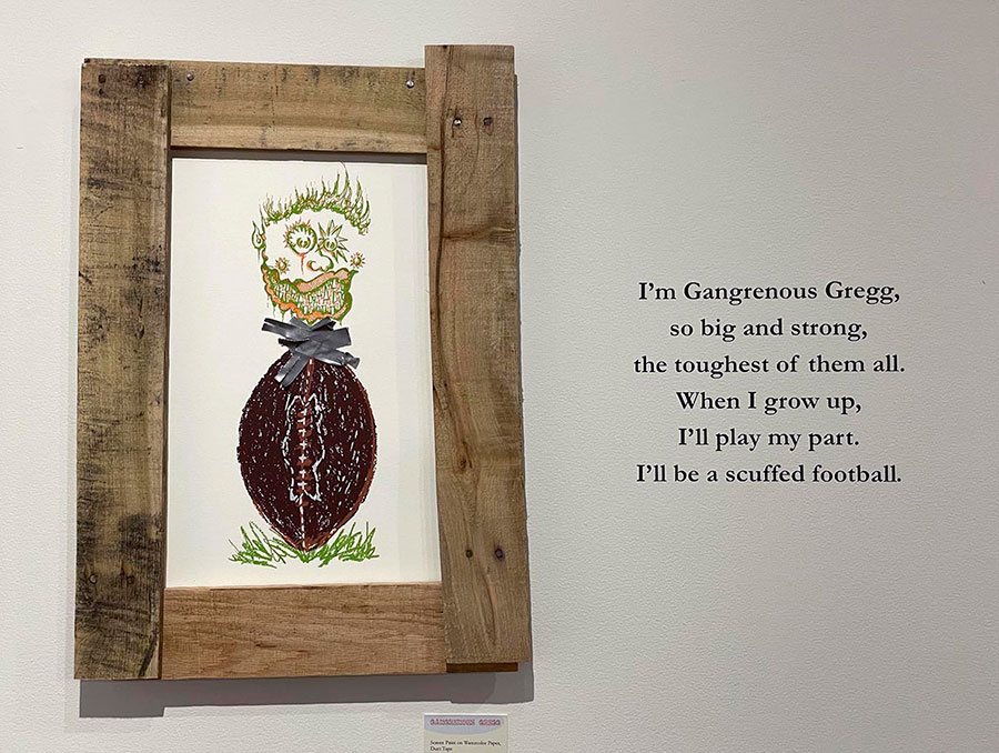 """Art piece in wooden frame of a drawing of a football with a head coming out of it hangs on wall next to quote, """"I'm Gangrenous Gregg, so big and strong, the toughest of them all. When I grow up, I'll play my part. I'll be a scuffed football."""""""