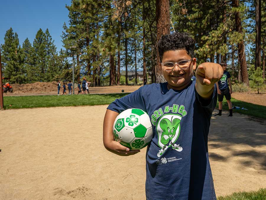 Youth holding a soccer ball and pointing at the camera.