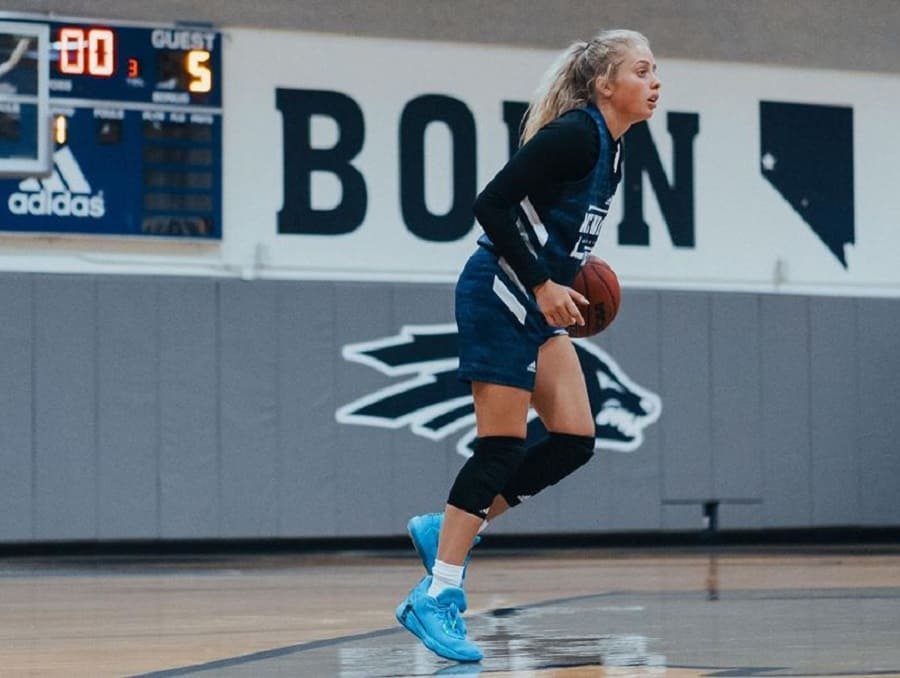 Kylie Jimenez with a basketball on the court at practice