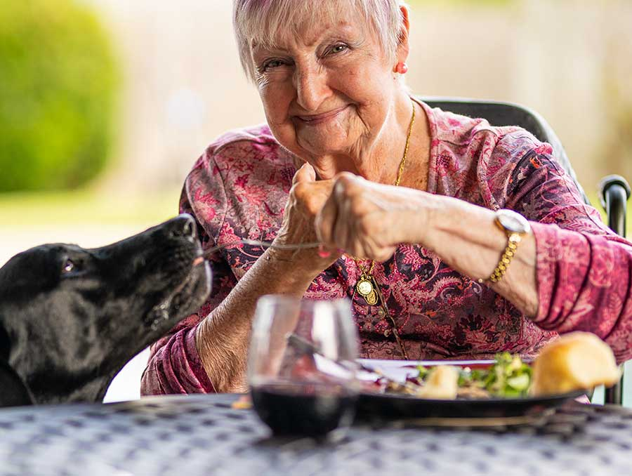 An older adult with pink hair smiles as she shares a bite of food from her meal with a big black dog.