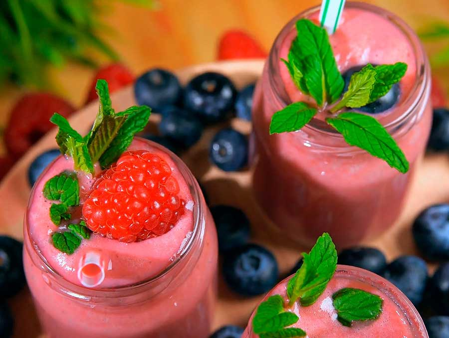 Three glass canning jars filled with raspberry smoothies topped with mint leaves, raspberries and blueberries.