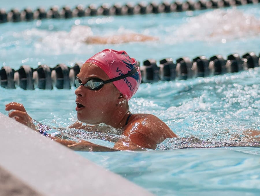 Mariana Vignoli swimming hard in the pool at practice, just about to finish a lap and turn around