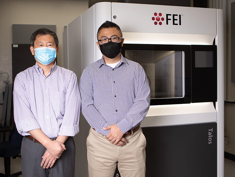 Two professors in masks standing in front of electron microscope