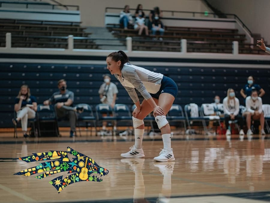 Andrea Alcaraz on the volleyball court during a game with the Athletics sport wolf logo decorated for Latinx Heritage Month