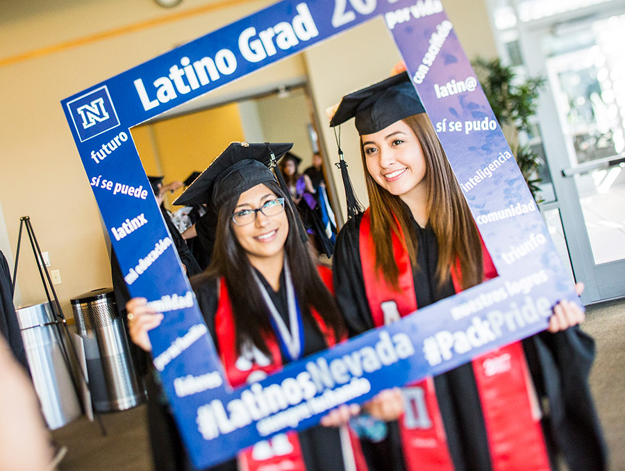 """Two students at graduation holding blue picture frame that says """"latino grad"""""""