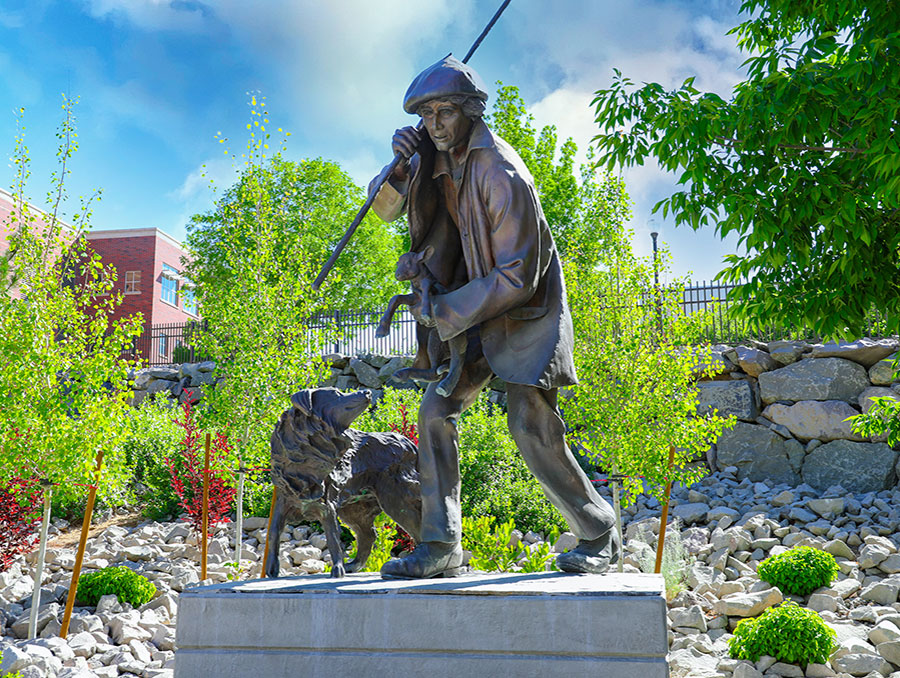 Statue of Basque Sheepherder holding lamb with dog by his side