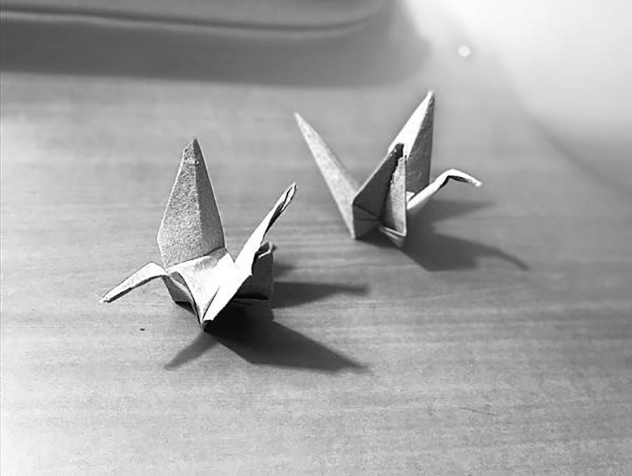 Black and white image of origami cranes made from retired military uniforms