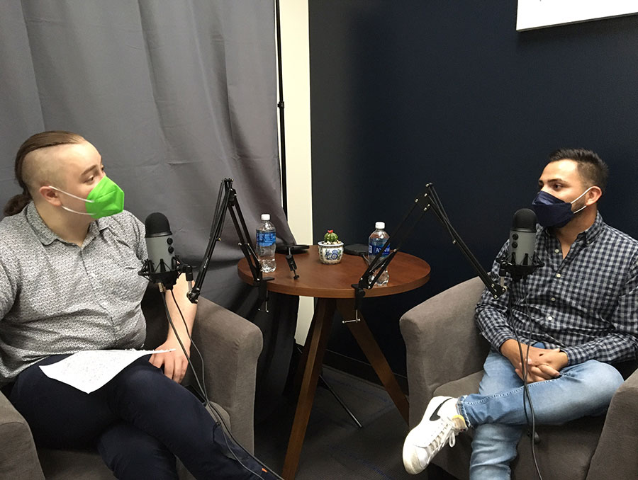 Two people sit at table talking and recording podcast