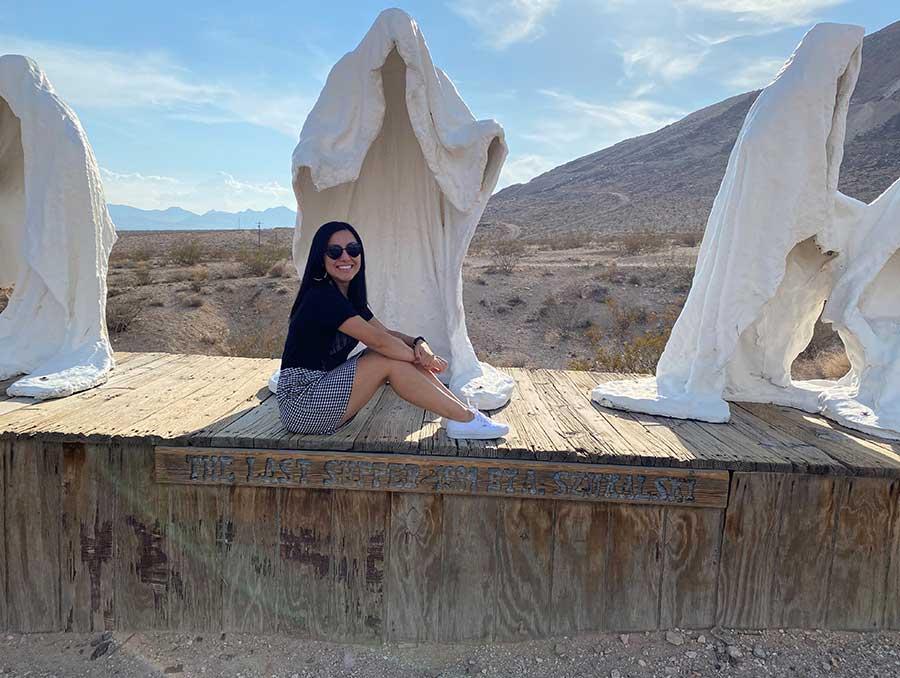 Jennifer Burton sitting on the ledge in front of art sculptures