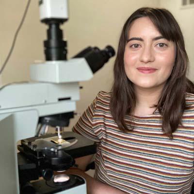 Photo of Sarah Trubovitz standing next to a microscope.