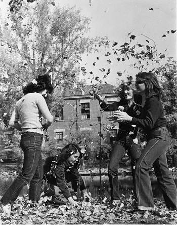 Female sorority members playing with leaves on campus