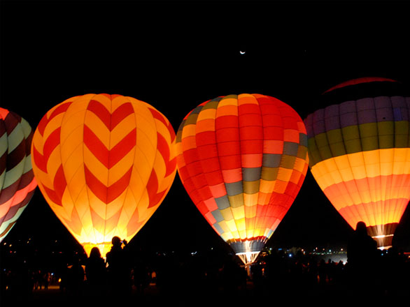 Three hot air balloons glow red as they are filled with fire in the darkness before the Reno-Tahoe balloon races