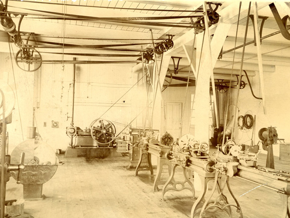 Image of a mechanical workshop from 1908 that includes pulleys, levers and other unnamed mechanical devices