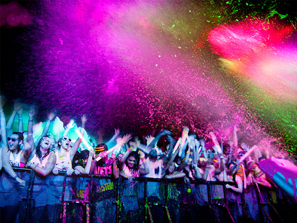 Neon paint with vibrant colors of pink and purple shades fills the air and splatters on a group of partygoers at a Reno Events paint the night celebration
