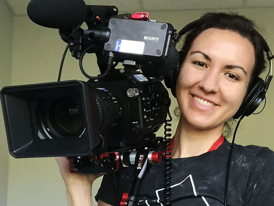 A student holding a TV camera, wearing a headset and smiling.