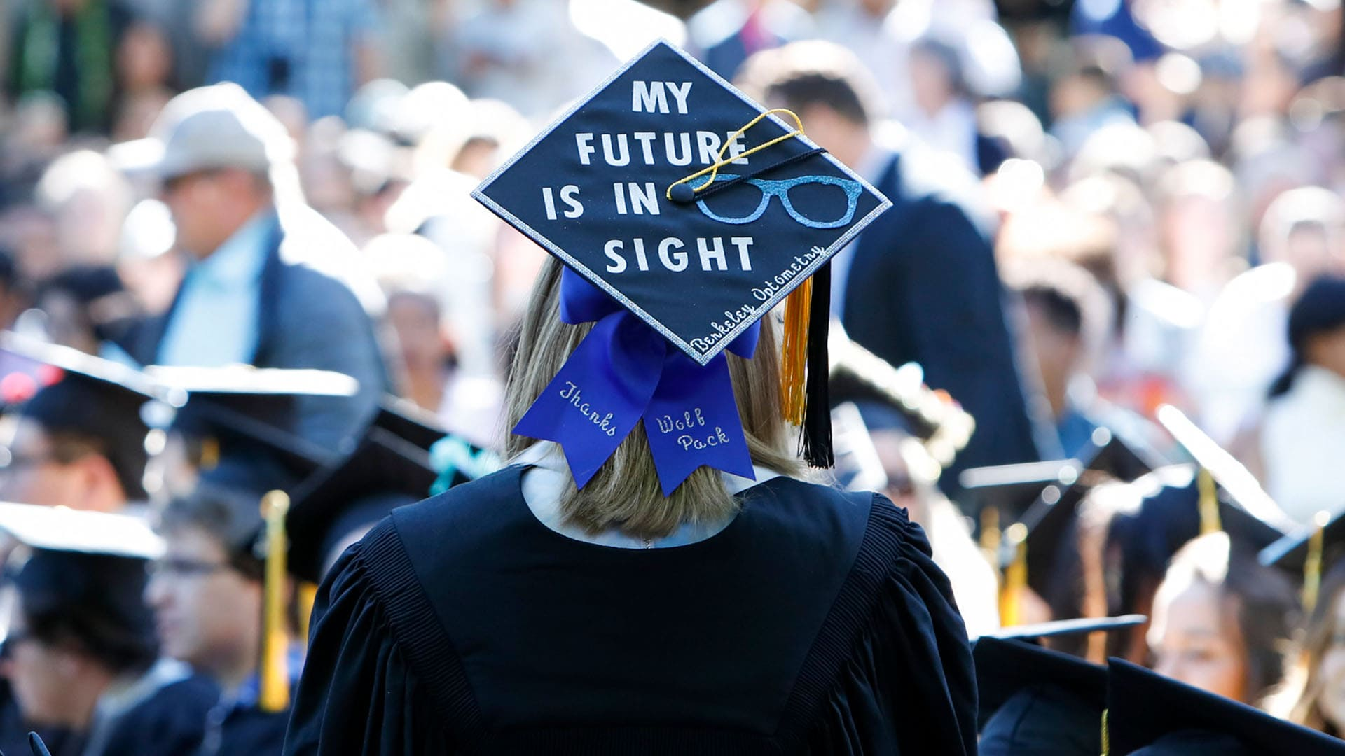 """A student wearing a mortar board with the words """"My future is in sight"""" stands among a crowd of graduating students."""