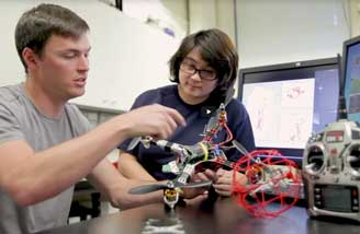 Two engineering sutdents work on a drone, with computers in the background