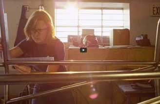 A student in an engineering lab working on a project; sunlight is streaming into the lab from a window behind the student