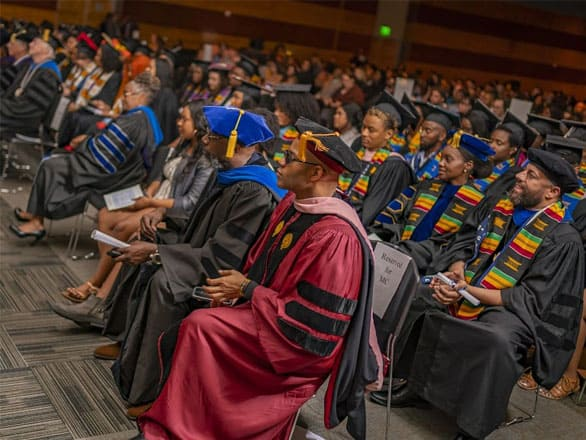 Faculty and graduates wear graduation attire and sit in rows at the the 2019 African Diaspora Graduate Celebration.