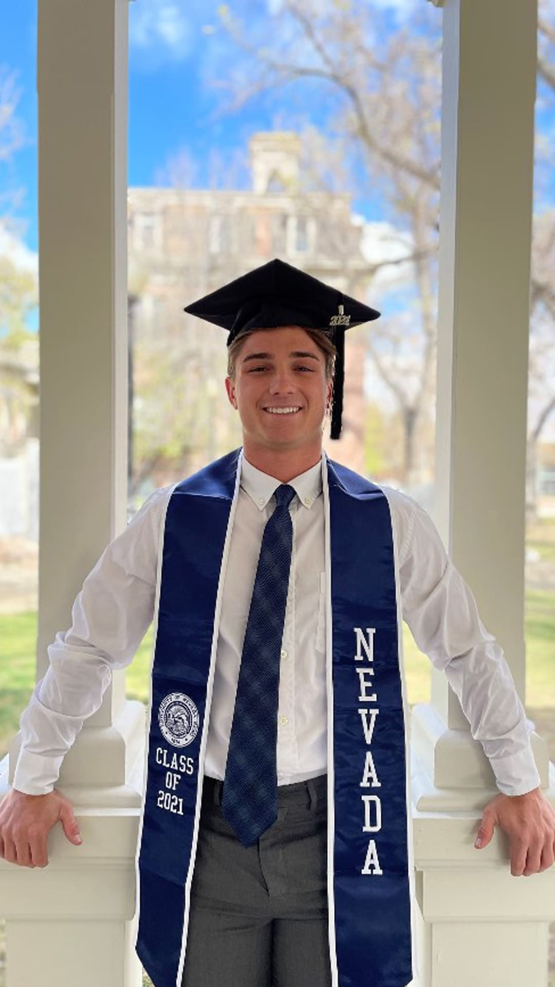 A student wears a tie and graduation regalia and poses for a picture while leaning against the railing at the Honor Court on the University of Nevada, Reno campus.