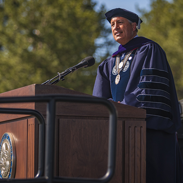 University President Brian Sandoval wears graduation attire and speaks at a podium during a commencement ceremony.