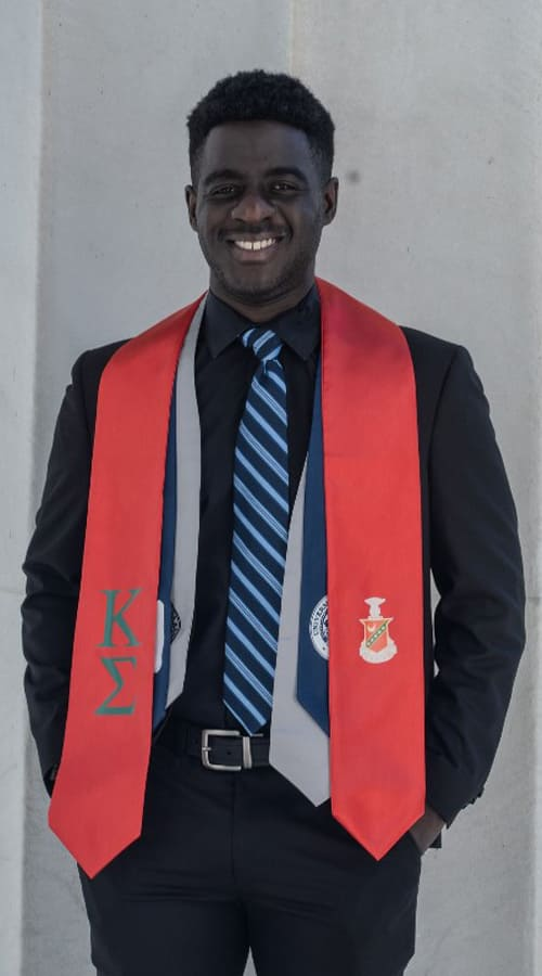 A student wears a suit and a red graduation hood and poses for a picture.