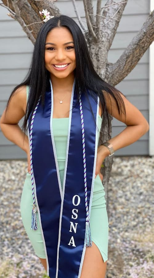 A student wears a dress and a blue graduation hood with the letters OSNA on it and poses in front of a tree and house for a picture.