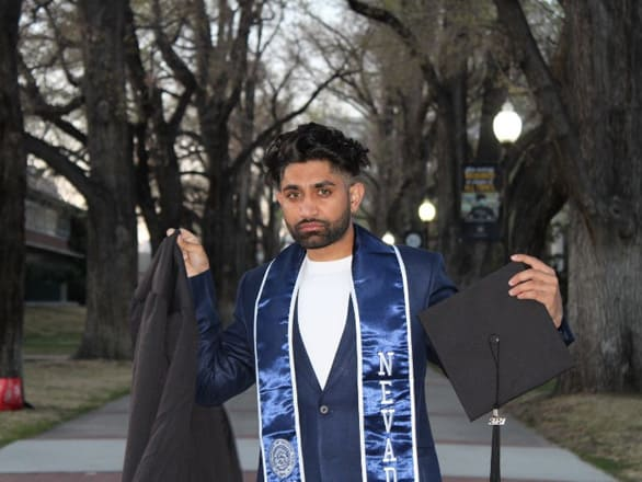 A student holds a mortar board and graduation gown and poses for a picture on the Quad at the University of Nevada, Reno.