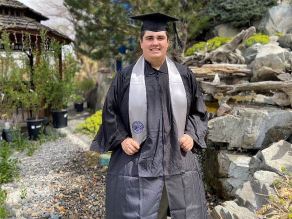 A student wears graduation attire and poses for a picture near a water feature in a private home's backyard.