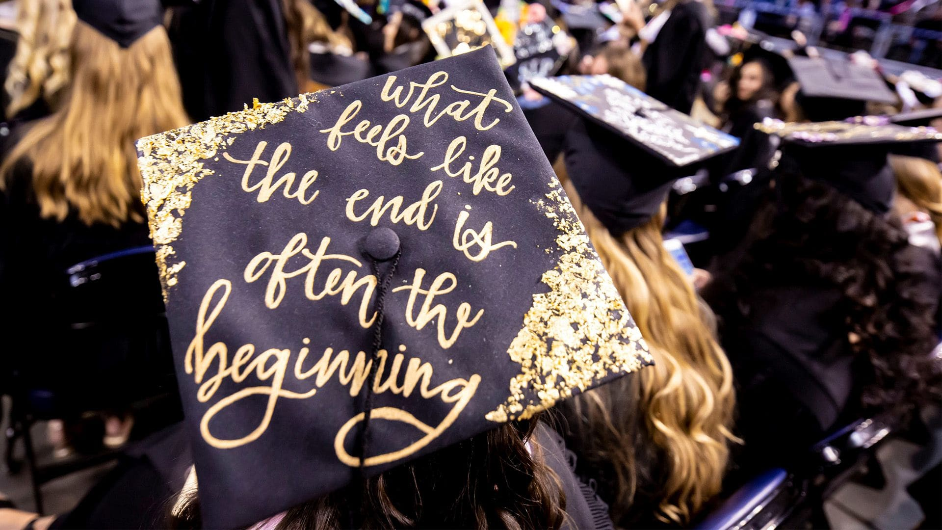 """A student wearing a mortar board that reads """"What feels like the end is often the beginning"""" sits next to other graduating students during a commencement ceremony."""