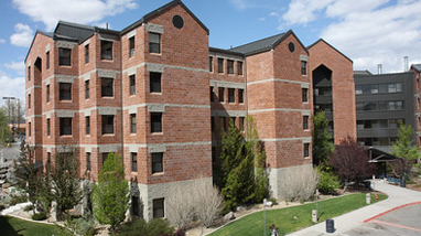 Exterior of Canada Hall, a modern multi-story brick residence halls with grass landscaping on the campus of the University of Nevada, Reno.