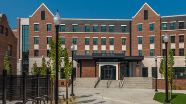 An exterior of Great Basin Hall, a residence hall at the University of Nevada, Reno, a modern brick building with multiple floors, concrete pathways, and trees in front of the building.
