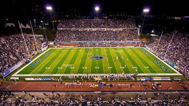 Mackay Stadium, on the campus of the University of Nevada, Reno campus, during an evening football game with thousands of fans in the stands, a green field and the University of Nevada, Reno logo in the middle of the field.