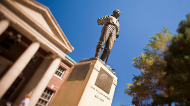 Image of the John Mackay statue on a pedestal standing in front of the Mackay School of Mines, a brick building with large white columns.