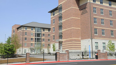 Exterior of the Nevada Living Learning Community, a modern brick building residence hall, on the campus of the University of Nevada, Reno.