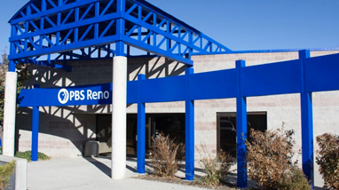 "Exterior of the PBS Reno building, a concrete building with blue steel beams surrounding the building and the words ""PBS Reno"" and logo on the beam in front of the door."